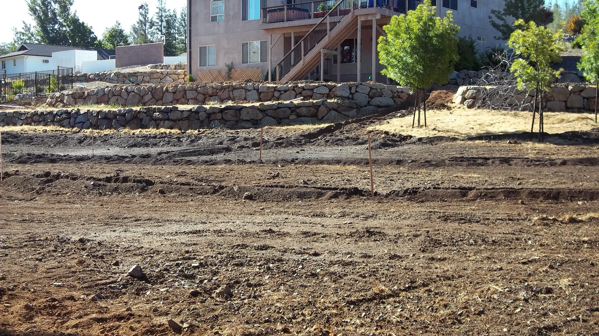Land in front of house makes with wooden poles and leveled out.