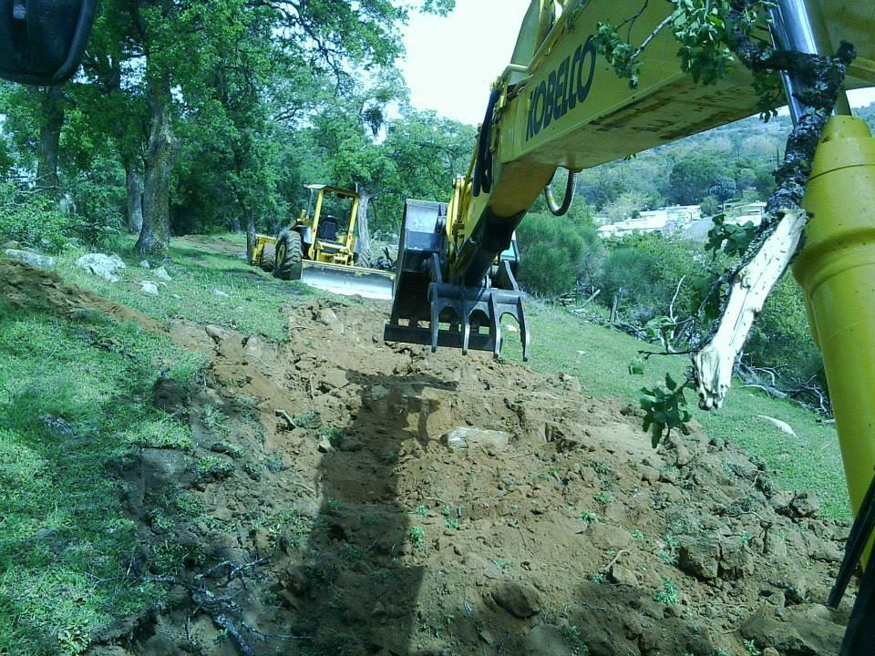 Arm of excavator and loader digging in countryside land.